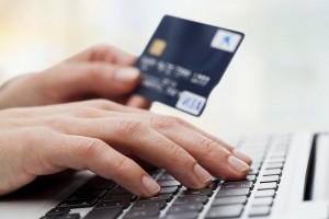 hands holding credit card while online shopping on laptop